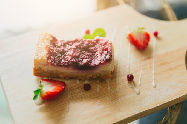 Cheesecake alla fragola su legno nella deliziosa torta fruttata gustosa caffetteria