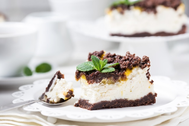 Cheesecake alla vaniglia con marmellata e biscotti di pasta frolla al cioccolato su un piatto bianco
