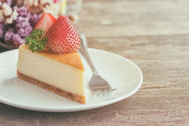Cheesecake casalingo di new york sul piatto bianco decorato da fragola e prezzemolo.