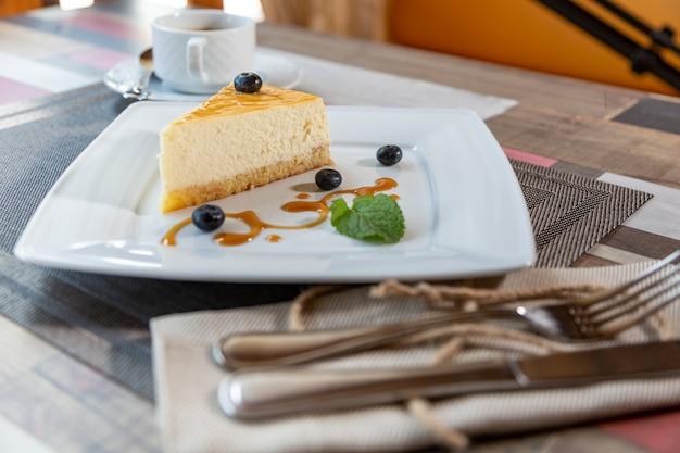 Cheesecake con salsa di mirtilli sul piatto bianco e tazza di caffè sul tavolo di legno