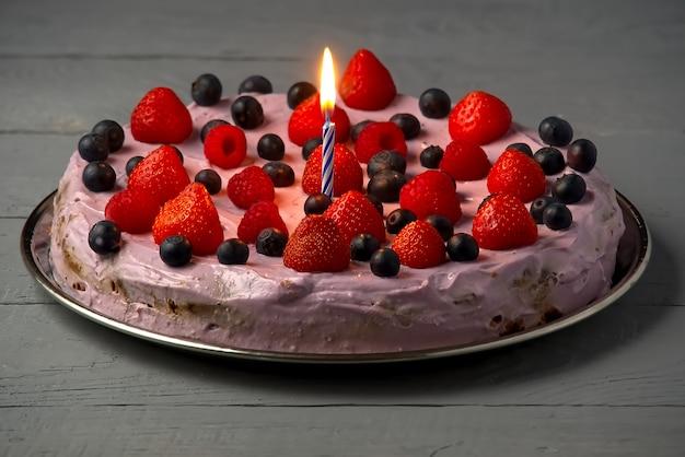 Cheesecake di compleanno fatta in casa con frutti di bosco e candele di compleanno. cheesecake con fragole, mirtilli e lamponi.