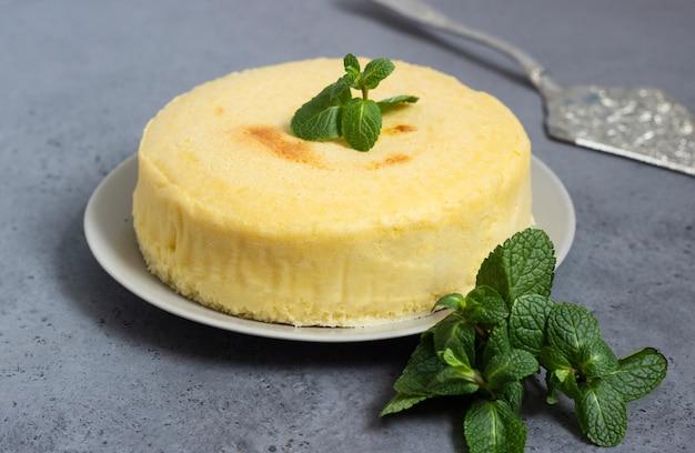 Cheesecake di cotone giapponese con menta su un piatto grigio.