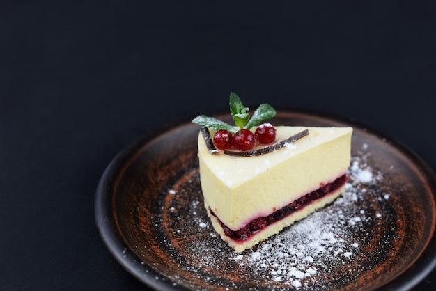 Cheesecake di dessert con menta e frutti di bosco su un nero con fiori
