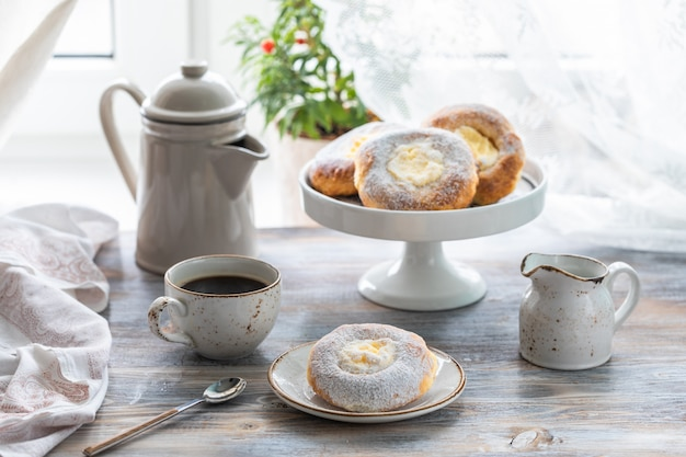 Cheesecake rotoli per colazione su un tavolo di legno vicino alla finestra con un gatto