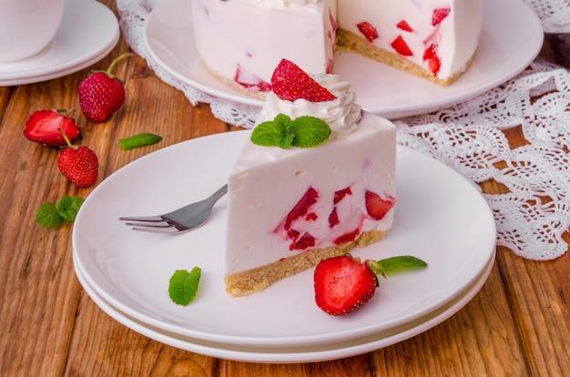 Cheesecake senza cottura alla fragola su fondo di legno scuro. stile rustico.