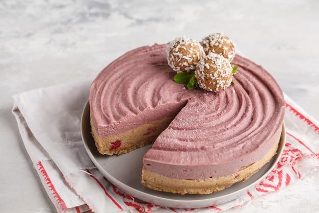 Cheesecake vegano crudo al caramello ai frutti di bosco con palline crude dolci al cocco. concetto di cibo vegano sano.