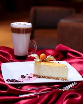 Cheesecake vista frontale decorato con una bacca su un piatto e con una tazza di ritardo