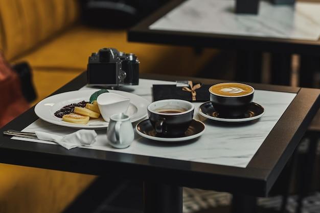 Cheesecakes a colazione con marmellata, cappuccino ed espresso e macchina fotografica. banner per bar e ristoranti