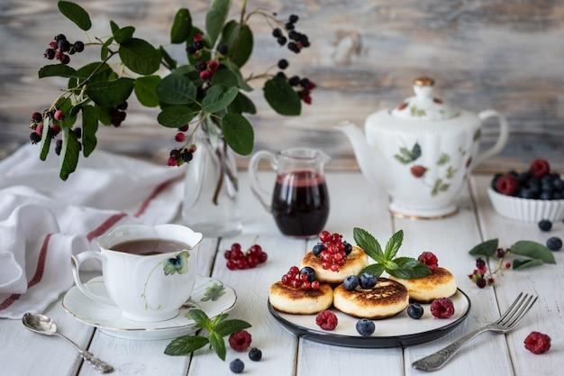 Cheesecakes di ricotta con frutti di bosco con un ramo di frutti di bosco irga.