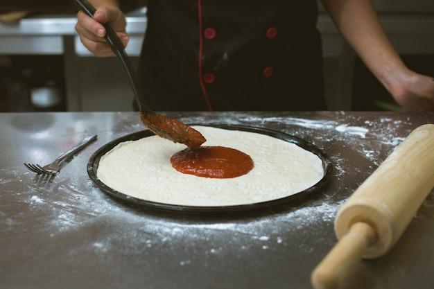 Chef a preparare la pizza in cucina