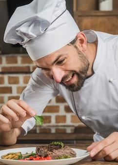 Chef che guarnisce il suo piatto con foglia di coriandolo