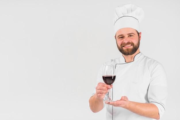 Chef che offre un bicchiere di vino