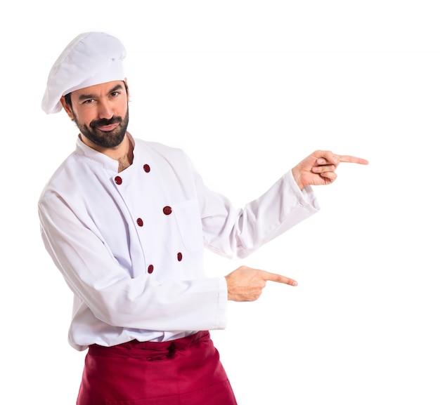 Chef che punta alla parte laterale su sfondo bianco
