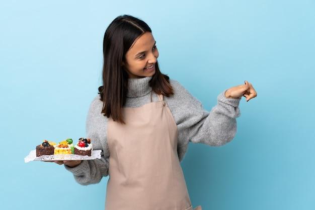 Chef che tiene una grande torta che dà un pollice in alto gesto