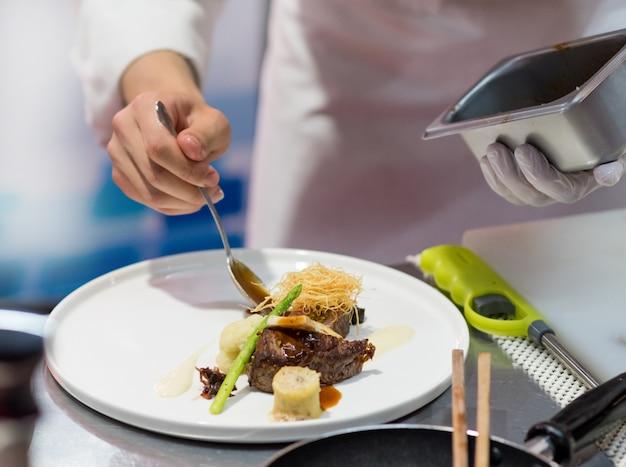 Chef cucina cibo in cucina, chef prepara cibo