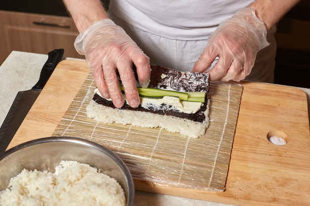 Chef fare sushi. preparazione di rotoli con nori, riso e cetriolo