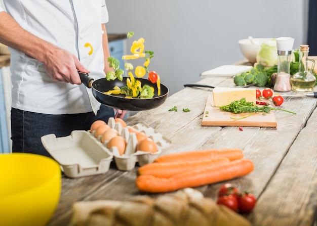 Chef in cucina cucinare con verdure