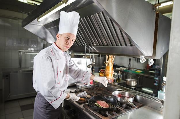 Chef in cucina del ristorante a piano cottura con padella, cottura