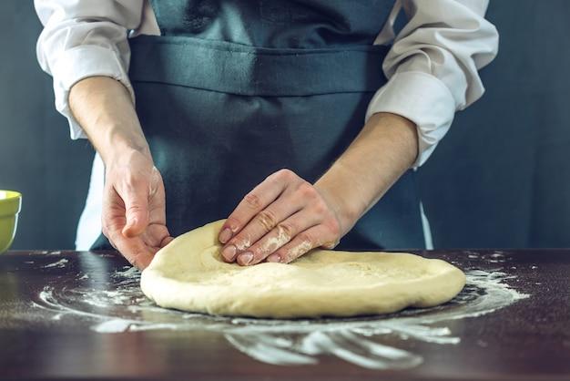 Chef in grembiule nero che impasta la pasta della pizza