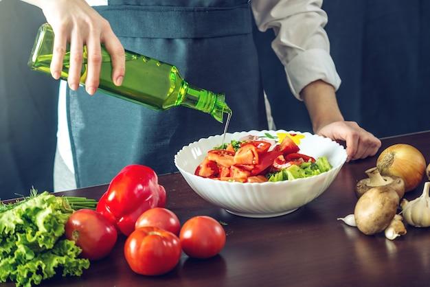 Chef in grembiule nero che prepara un'insalata di verdure