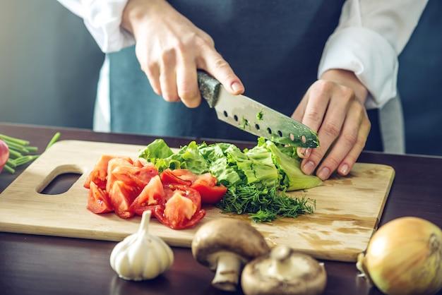 Chef in grembiule nero tagliare le verdure