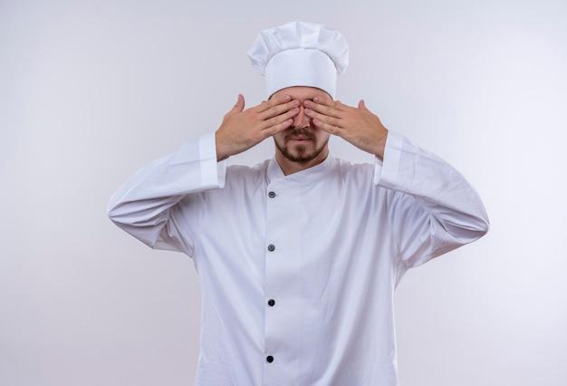 Chef maschio professionista cuoco in uniforme bianca e cappello da cuoco che copre gli occhi con le mani in piedi su sfondo bianco