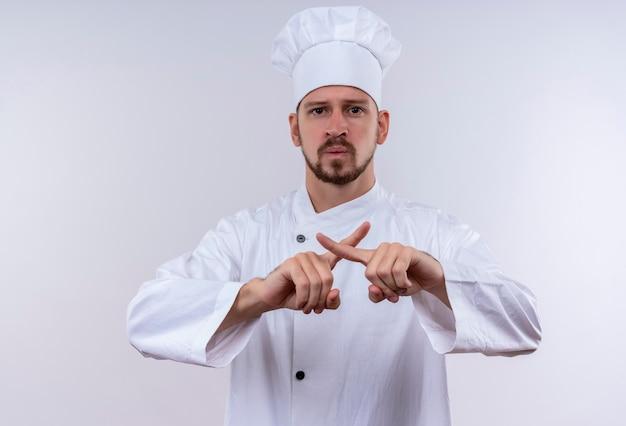 Chef maschio professionista cuoco in uniforme bianca e cappello da cuoco che fa gesto di difesa incrociando le dita dell'indice in piedi su sfondo bianco