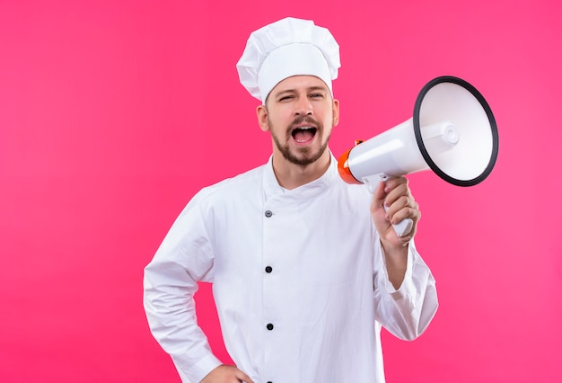 Chef maschio professionista cuoco in uniforme bianca e cappello da cuoco che grida al megafono in piedi su sfondo rosa