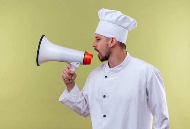 Chef maschio professionista cuoco in uniforme bianca e cappello da cuoco che grida al megafono in piedi su sfondo verde