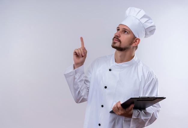 Chef maschio professionista cuoco in uniforme bianca e cappello da cuoco che tiene appunti con pagine vuote che punta il dito verso l'alto ricordando cosa importante in piedi su sfondo bianco