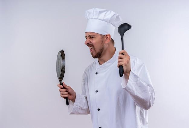 Chef maschio professionista cuoco in uniforme bianca e cappello da cuoco che tiene padella e mestolo gridando e urlando con espressione aggressiva in piedi su sfondo bianco