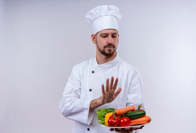 Chef maschio professionista cuoco in uniforme bianca e cappello da cuoco che tiene un piatto con le verdure, facendo gesto di difesa con la mano in piedi su sfondo bianco