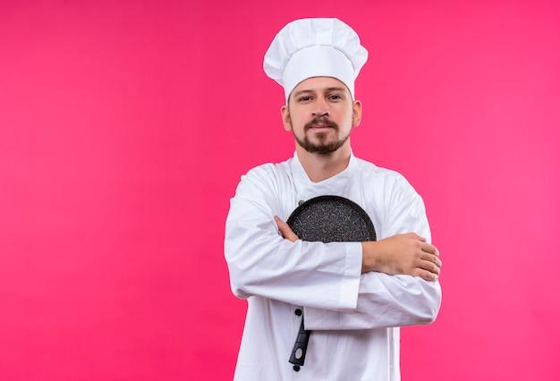 Chef maschio professionista cuoco in uniforme bianca e cappello da cuoco che tiene una padella con le braccia incrociate guardando fiducioso e orgoglioso in piedi su sfondo rosa