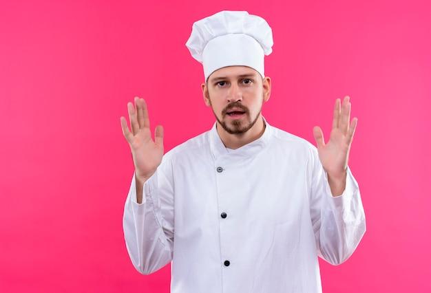 Chef maschio professionista cuoco in uniforme bianca e cappello da cuoco gesticolando con le mani che mostrano le dimensioni, simbolo di misura su sfondo rosa