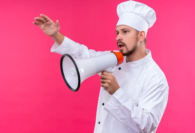 Chef maschio professionista cuoco in uniforme bianca e cappello da cuoco parlando al megafono chiamando qualcuno che fluttua con la mano in piedi su sfondo rosa