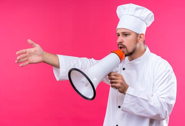 Chef maschio professionista cuoco in uniforme bianca e cappello da cuoco parlando al megafono gesticolando con la mano in piedi su sfondo rosa
