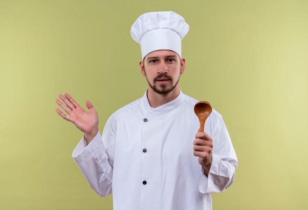 Chef maschio professionista cuoco in uniforme bianca e cappello da cuoco tenendo il cucchiaio di legno alzando la mano guardando fiducioso in piedi su sfondo verde