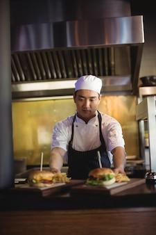 Chef posizionando il vassoio con patatine fritte e hamburger alla stazione di ordinazione
