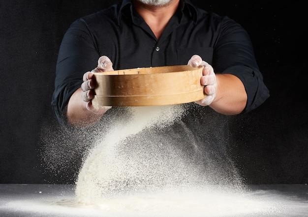 Chef un uomo in uniforme nera tiene in mano un setaccio di legno rotondo e setaccia la farina di frumento bianco