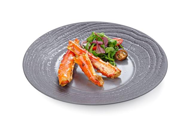 Chele di granchio cotte con insalata isolata su bianco