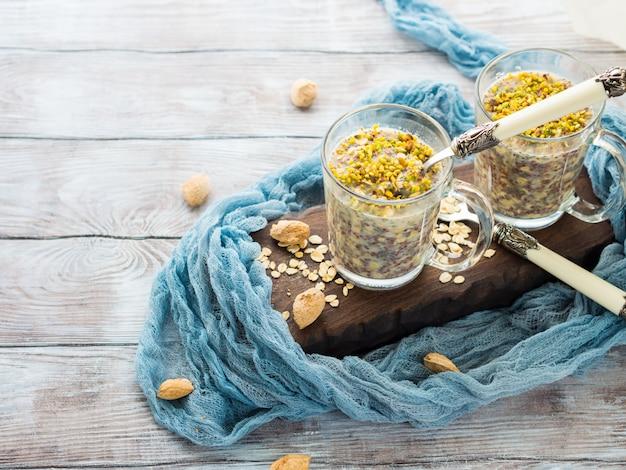 Chia arrotolato porridge di avena durante la notte con quinoa, banana, pistacchi, latte. una sana colazione in tazza