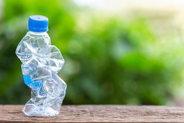 Chiara bottiglia di plastica vuota sulla tavola o sul contatore di legno con il fondo verde della sfuocatura della luce della natura