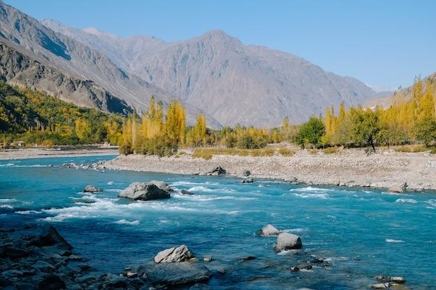 Chiaro fiume di acqua blu turchese che scorre lungo la catena montuosa hindu kush in autunno.