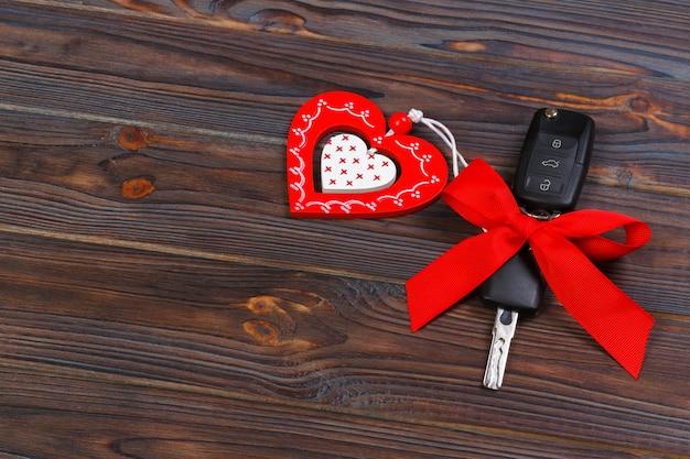Chiave dell'automobile con cuore rosso su sfondo naturale nero.
