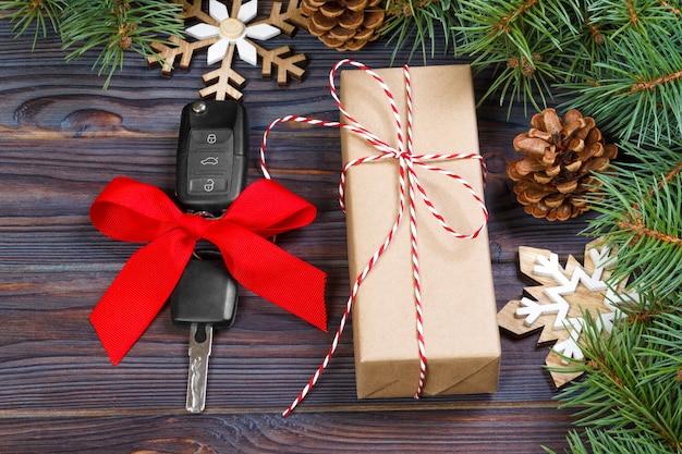 Chiave dell'automobile con l'arco variopinto con il contenitore di regalo e la decorazione di natale su di legno
