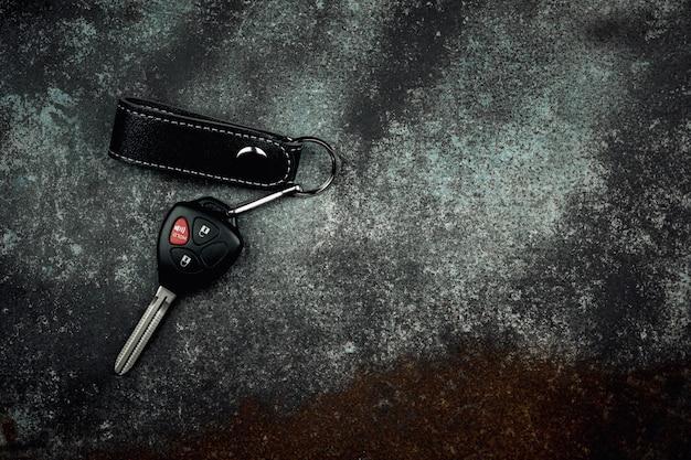 Chiave dell'automobile con telecomando sul vecchio e pavimento abbandonato del metallo.