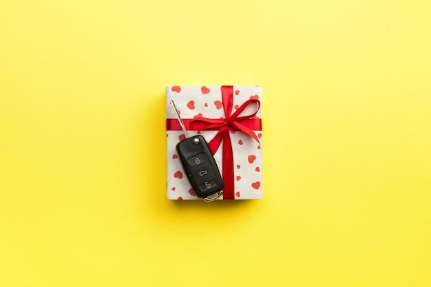 Chiave dell'automobile sul contenitore di regalo di carta con l'arco e cuore rossi del nastro su giallo