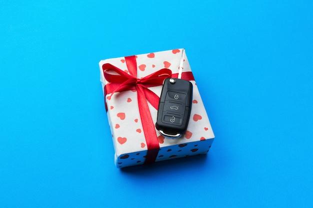 Chiave dell'automobile sul contenitore di regalo di carta con l'arco e cuore rossi del nastro sul fondo blu della tavola.