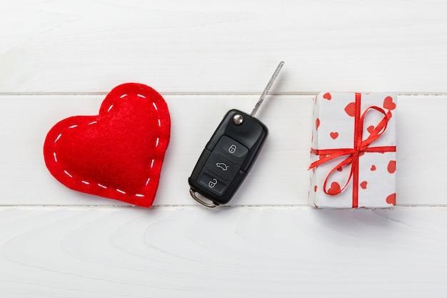 Chiave dell'automobile sul contenitore di regalo di san valentino e sui cuori rossi