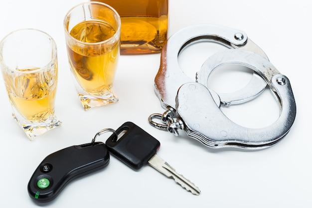 Chiave dell'automobile sulla barra con alcool versato